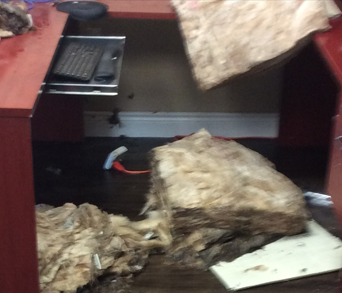 Saturated insulation that fell from a ceiling onto a red desk