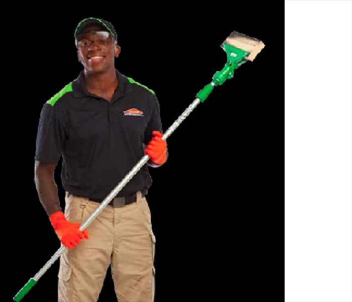Male technician in black SERVPRO shirt with khakis holding a sponge brush