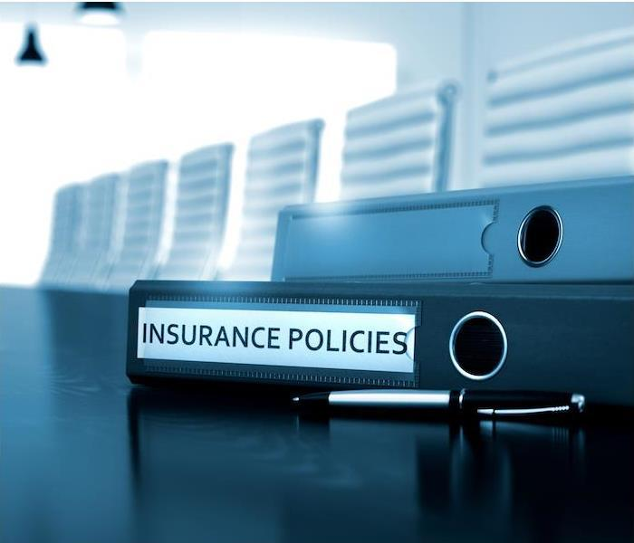 insurance policies binders and pen sitting on black table in large conference room
