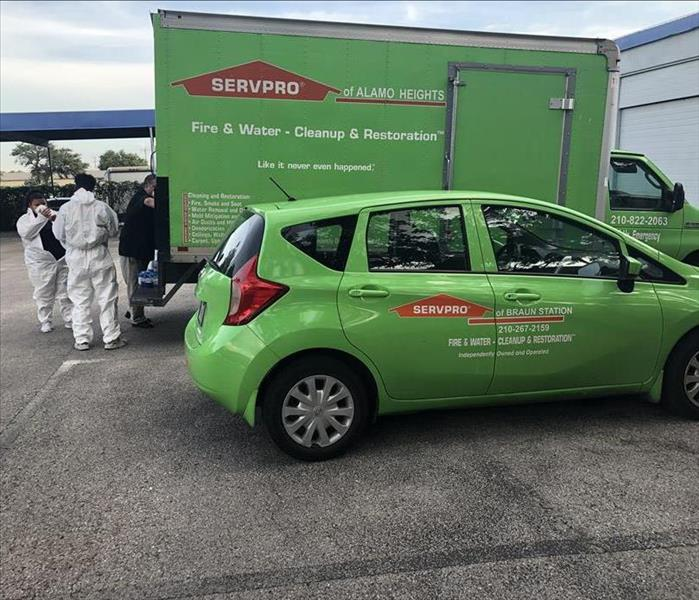3 people donning PPE in front of a large green box truck and a SERVPRO® green hatchback