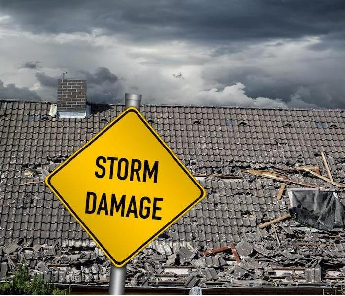 a yellow storm damage sign in front of a large damaged roof""