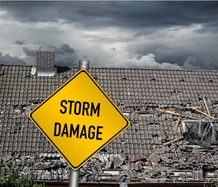 a yellow storm damage sign in front of a large damaged roof